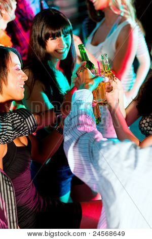 Dance action in a disco club - group of friends, men and women of different ethnicity, dancing to the music having lots of fun