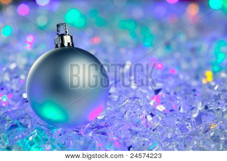 christmas silver bauble on colorful glowing ice cubes