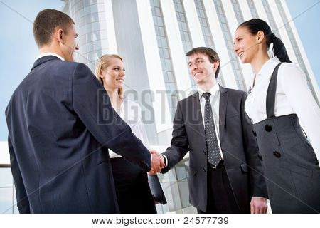Business handshake of two successful partners at modern building
