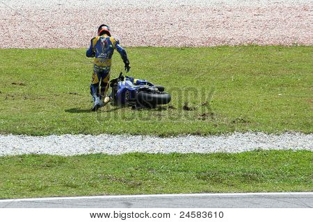 SEPANG, MALAYSIA - OCTOBER 23: Moto2's Mike di Meglio runs to his bike after a fall at turn 15 during warm-up at the Shell Advance Malaysian Motorcycle GP 2011 on October 23, 2011 at Sepang, Malaysia.