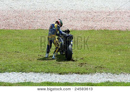 SEPANG, MALAYSIA- OCTOBER 23: Moto2's Mike di Meglio picks up his bike after a fall at turn 15 during warm-up at the Shell Advance Malaysian Motorcycle GP 2011 on October 23, 2011 at Sepang, Malaysia.