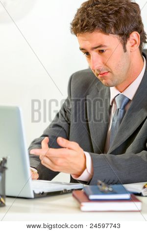 Confused Modern Businessman Sitting At Office Desk Working On Laptop