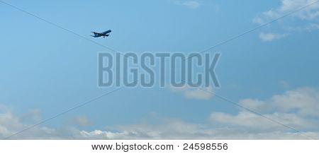 Plane Preparing For Landing Flying Through Blue Sky
