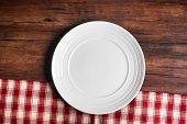 Empty White Plate On A Checkered Red Napkin On An Old Wooden Brown Background, Top View. Image With  poster