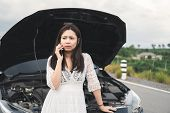Stressed Asian Woman With A Broken Car Using Mobile Phone To Call Assistance On Roadside. Accident A poster