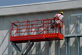 foto of boom-truck  - Constuction worker works on high scaffolding at a construction site - JPG