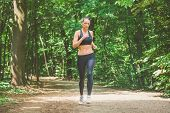 Young Female Athlete Jogging In Forest. Jogger Doing Morning Physical Training. poster