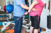 No Face Elderly Woman Doing Active, Special Exercises Guided By Physical Therapist At The Hospital R poster