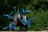 Race Drone With Blue Propellers And Transmitter With Green Background In Nature And Motors For Drone poster