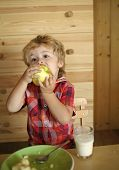Baby Eats An Apple In A Village Hut. Breakfast, Morning, Family. Small Boy Child Eat Banana And Drin poster