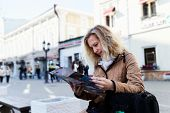 Woman Tourist Holding A Tourist Map Against Blurred Background. Tourist In Russia Discovering And Ex poster