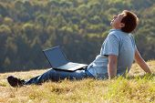 Young Man Using Laptop Sitting On The Grass On The Hillside