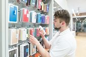 Man Chooses Cases To Store Accessories For Smartphones. Purchasing Accessories For A Smartphone In A poster
