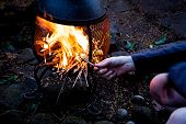 Man Sitting By The Open Fire And Firing With Wood Twigs. Camping Fire In The Twilight Night. Wooden  poster