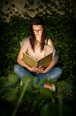 The Magic Of Books. Beautiful Yopung Brunette Immersed In Reading A Book, Portrait With Creative Lig