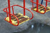 Red Metal Swing With A Wooden Seat On A Kids Playground On A Rainy Day With A Puddle Under It poster