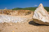 pic of oversize load  - Big stone in a quarry with an excavator on background - JPG