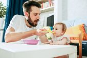 Good Looking Young Man Eating Breakfast And Feeding Her Baby Girl At Home poster