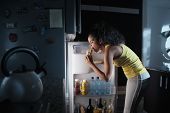 African American Woman Doing Midnight Snack At Home. She Eats A Sandwich And Looks For Food Into The poster