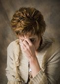 picture of sad faces  - troubled mature woman with hand on face - JPG