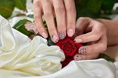 Female Hands Holding Red Roses. Girls Hand With Beautiful Manicure Holding Red Roses On White Silk.  poster