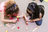 High-angle view of two pre-school girls sharing wooden toy blocks while building together a challeng poster