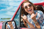 Excited Young Woman In Sunglasses Sitting In Car And Showing Thumbs Up During Trip poster