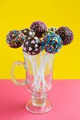 Chocolate Cake Pops In Glass, Decorated With Colorfull Confectionery Sprinkles On A Yellow Backgroun poster