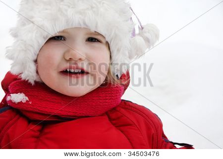 Happy Little Girl Wearing Warm Clothing Stands And Looks At Camera
