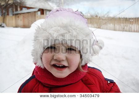 Cute Little Girl Wearing Warm Clothing Stands Near Home And Looks At Camera