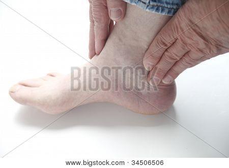 homem com as mãos no tornozelo