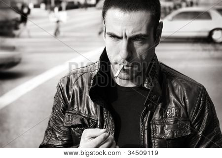 Vintage retro style black and white portrait of a tough sexy guy in leather jacket