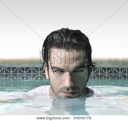 Sexy male model in swimming pool with copy space above