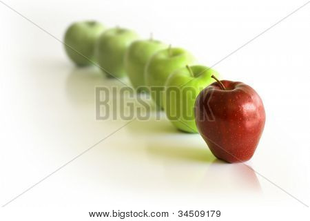 Line of green apples with red apple in front against neutral reflective background