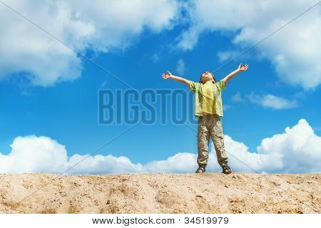 Happy Child Standing With Hands Raised Up Over Blue Sky On The Top. Happiness And Freedom Concept.