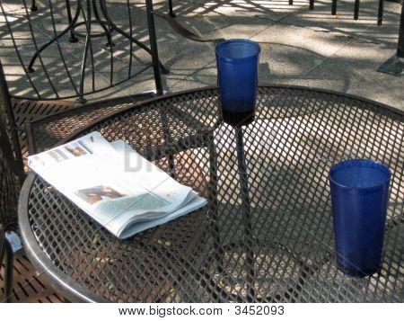 Newspaper And Drinks On Outdoor Table