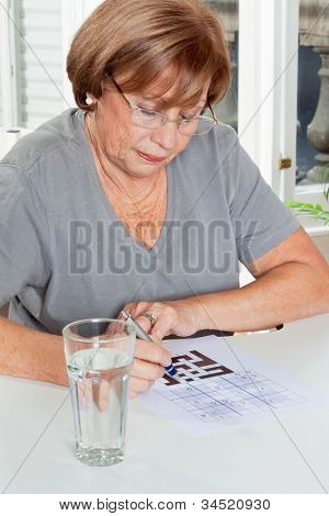 Senior woman playing leisure games with glass of water in foreground