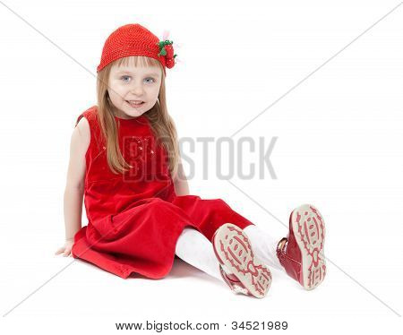 A Girl Aged Four Years In A Red Dress Sitting On The Floor