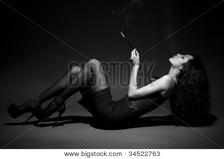 woman smokes in the dark. studio shot. space for text. BW Image