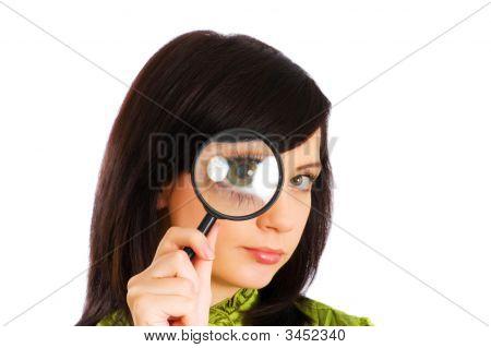 Ojos de la muchacha magnificado a través del cristal de Magnifiing en blanco