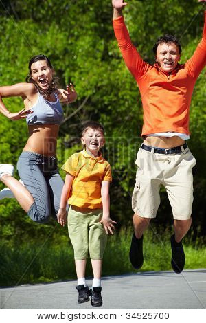 Dynamic shot of a sportive family jumping outdoors