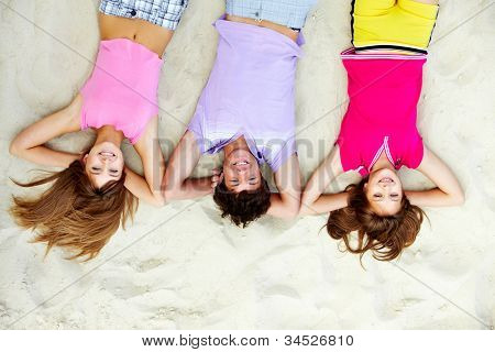 Above angle of laughing teenage friends lying on sandy beach
