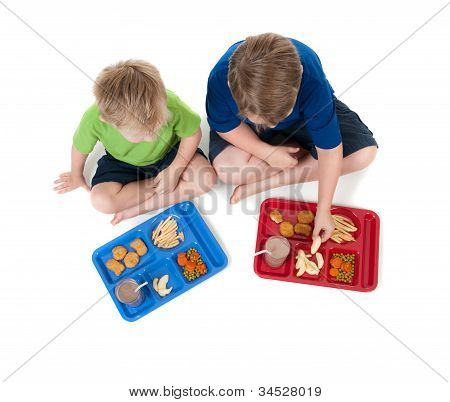 Two young boys eating school lunch on white