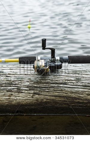 Fishing Reel On Log In Lake