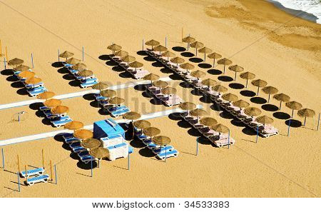 view of a beach with sunlounger and umbrellas in the summer