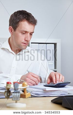 Business man at his desk using a calculator in the office