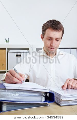 Manager working on files at his desk in his office