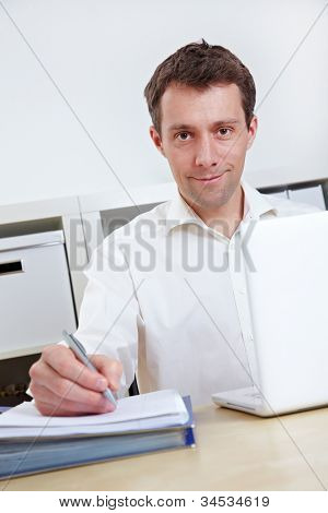 Business working with laptop and files at his desk in the office