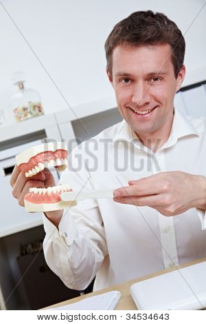 Smiling dentist in office offering tips for brushing teeth with toothbrush