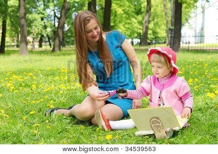 Girl And Mother Reading The Book In Park